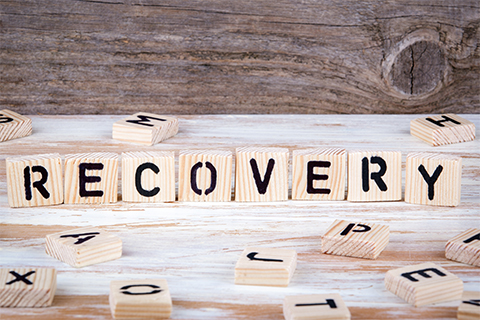 Image of scrabble pieces grouped together to spell the word recovery