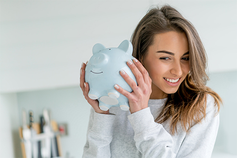 Image of a woman holding a piggy bank