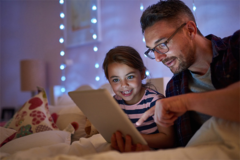 Image of a father reading to his child from an IPad