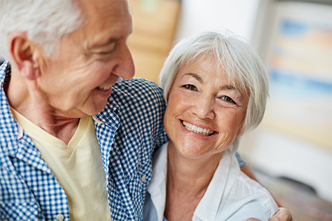Image of an elderly couple happily embracing