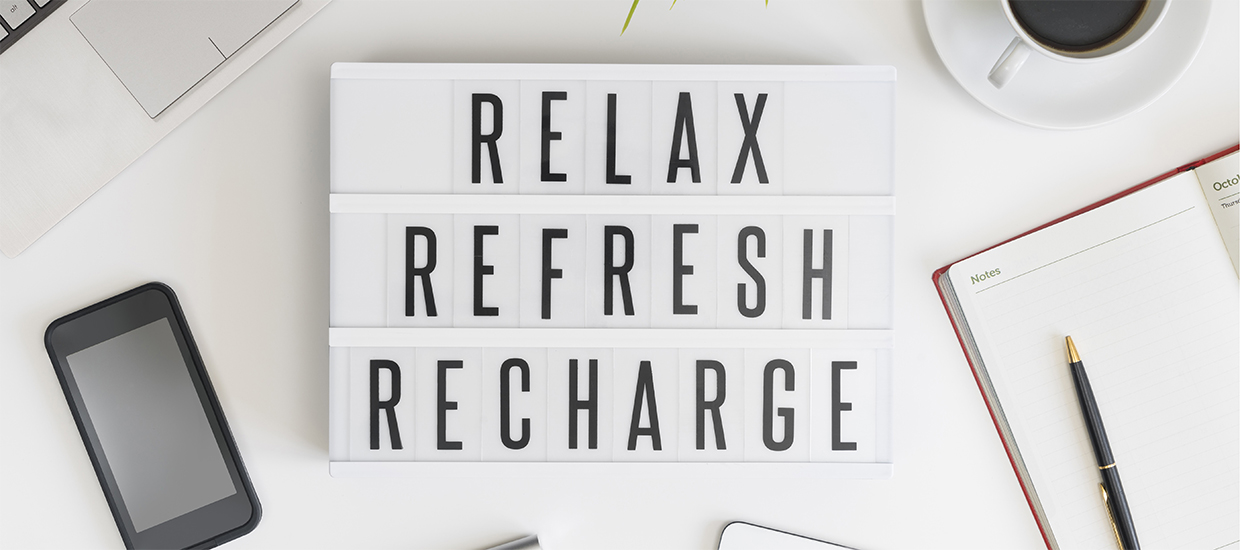 "Image of a sign reading ""Relax, Refresh, Recharge"" atop a workbench"